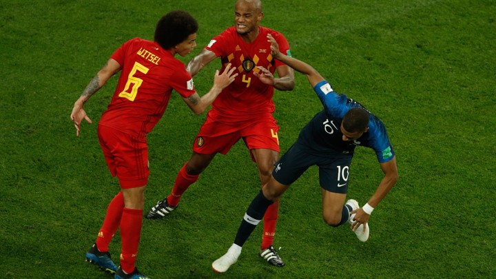 Three soccer players shoving each other