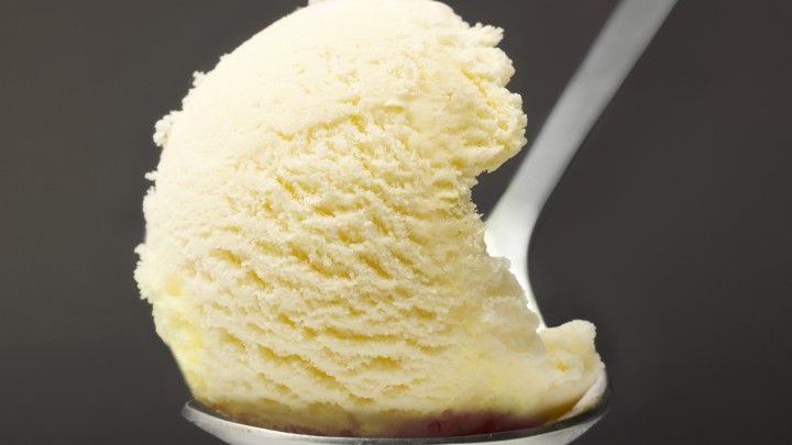 A scoop of vanilla ice cream rests on a spoon.