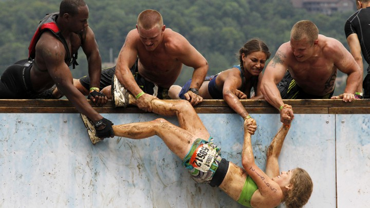 Athletes pull a mud-covered team member over a wall
