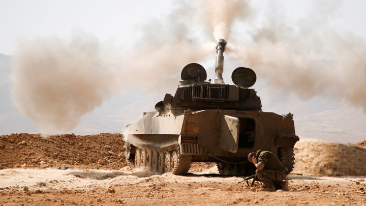 A Hezbollah fighters kneels next to a tank after firing his weapon in Syria