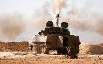 A Hezbollah fighters kneels next to a tank after firing his weapon in Syria.
