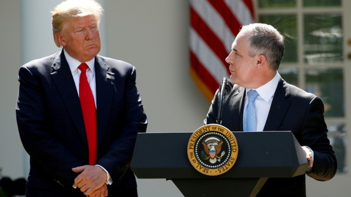 Scott Pruitt stands at a podium and addresses Donald Trump in the White House Rose Garden.