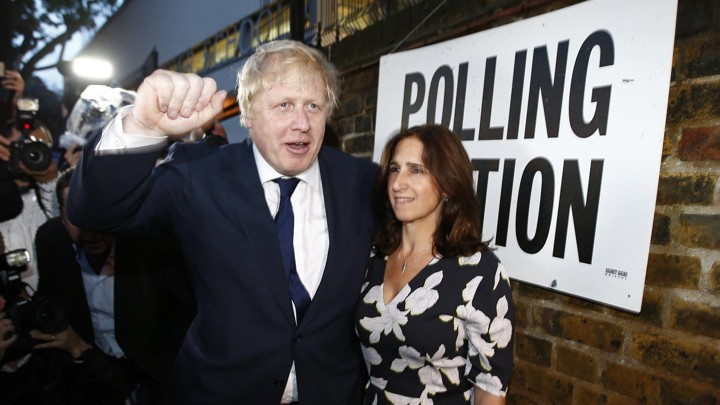 Boris Johnson raises his hand in a fist while standing with his wife outside a polling station on the day of the Brexit vote.