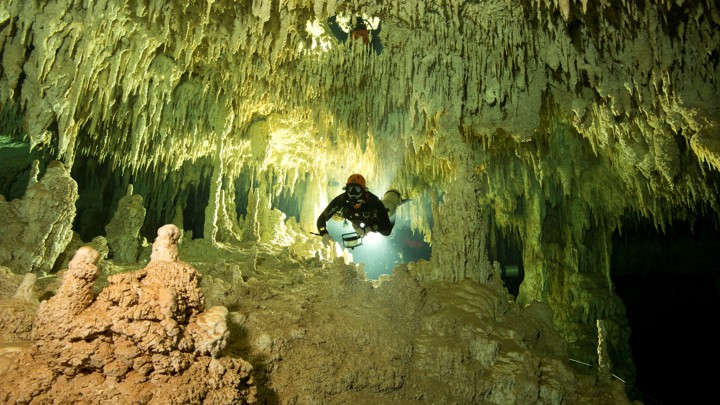 A scuba diver measures the length of an underwater green and brown cave system