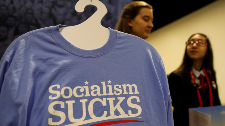 "A T-shirt on a hanger reads ""Socialism Sucks""; two young women stand behind it."