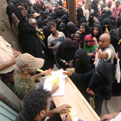 Several Hodeidah residents wait in front of a table, where workers distribute aid materials.