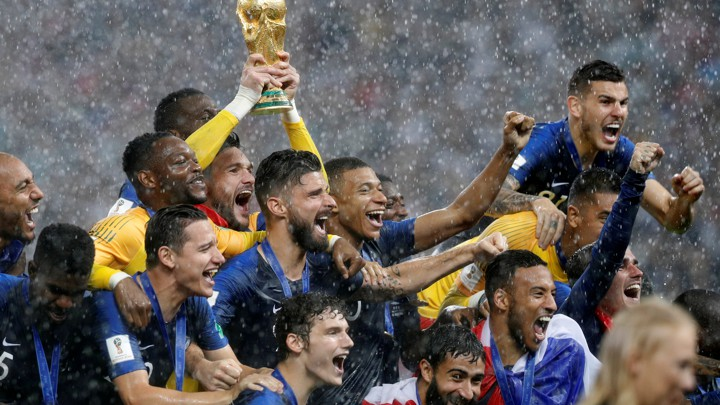 Members of the French national team hold up their World Cup trophy victoriously