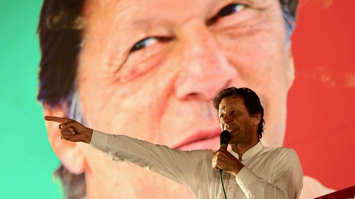 Imran Khan holds a microphone while standing in front of a backdrop with a photograph of his face at a campaign rally
