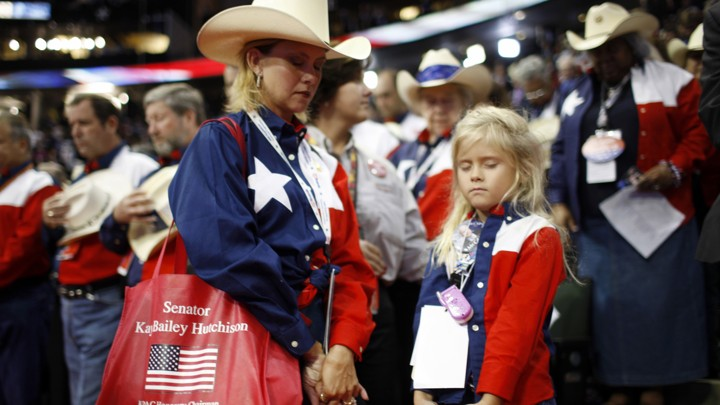 A woman and daughter dressed patriotically bow their heads in prayer