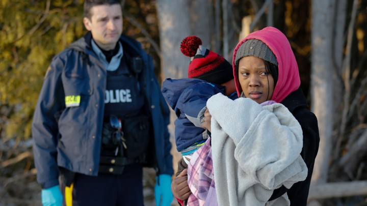 RCMP officer looks on as a woman carrying a child waits to cross the U.S.-Canada border.