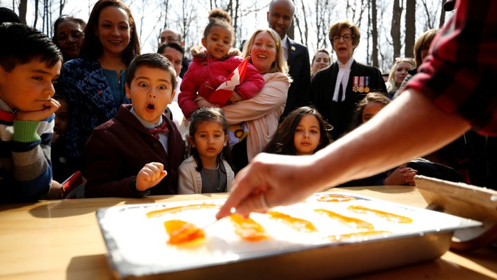 New Canadian citizens react as maple taffy is prepared following a citizenship ceremony in 2018