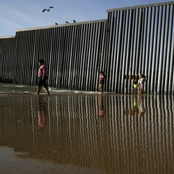 The border wall separating Tijuana and San Diego is reflected in the Pacific Ocean