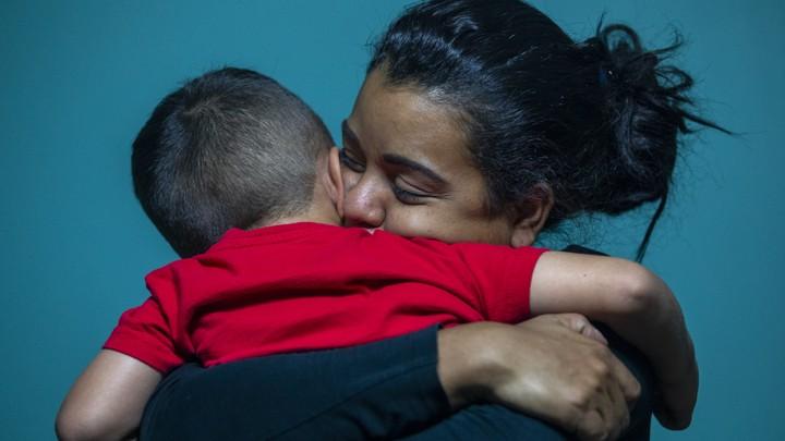A woman hugs a small boy