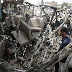 A man looks at the shell of a bus that had been destroyed in a Saudi air strike in Yemen.