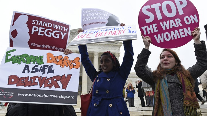 Three women holding signs stand in front of the Supreme Court, protesting a decision