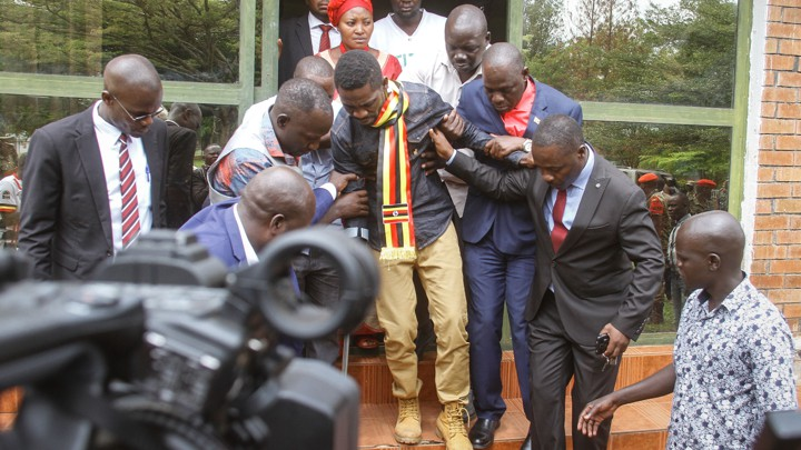 Bobi Wine walks with several other people supporting him.