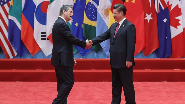 Director-General of the World Trade Organization Roberto Azevêdo shakes hands with Chinese President Xi Jinping on a red stage in front of several countries' flags at the G20 Summit in 2015.