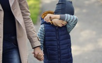 A boy holds his arm in front of his face while holding hands with a woman