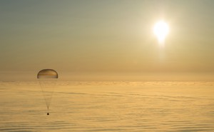 An astronaut capsule with a parachute floats down to Earth.