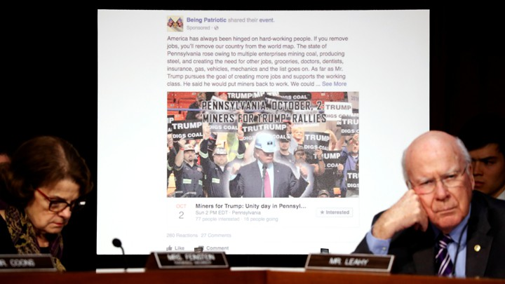 Senators Dianne Feinstein and Pat Leahy sit in front of a screen showing a fake Facebook page created by Russia during the 2016 election.
