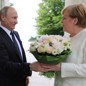 Putin hands Merkel a bouquet of flowers while shaking her hand at a meeting in Sochi.