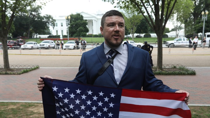 White-nationalist leader Jason Kessler poses with a flag across from the White House.