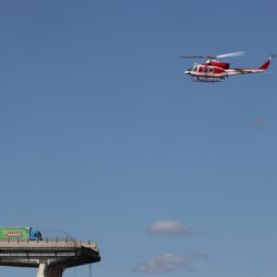 A firefighter helicopter flies above the destroyed Morandi bridge, where a truck pauses just before the section that broke apart.