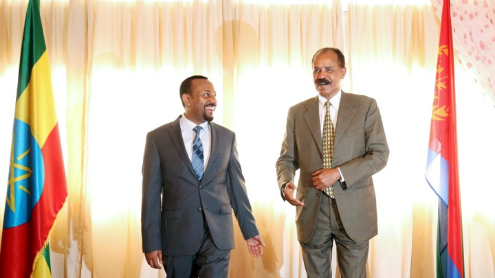 Ethiopian President Abiy Ahmed laughs next to Eritrean President Afwerki, between flags from their two countries, at the reopening of the Eritrean Embassy in Addis Ababa.