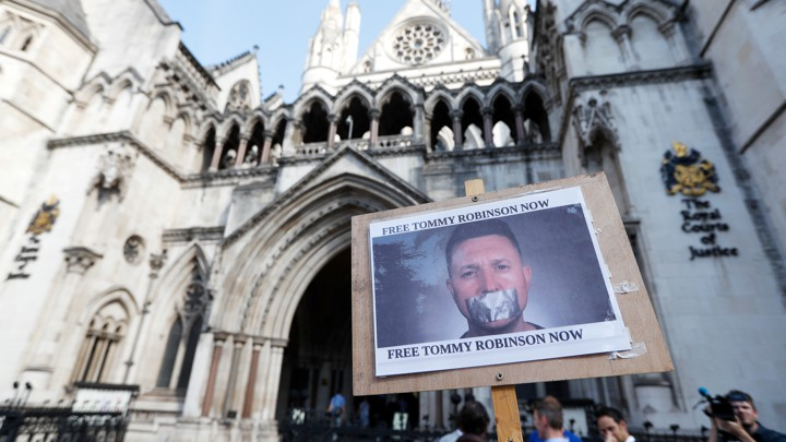 "Protesters hold up a placard saying ""Free Tommy Robinson Now"" outside the Royal Courts of Justice in London on August 1, 2018"