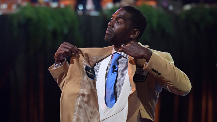 Randy Moss reacts after receiving a gold jacket during the enshrinee's gold-jacket dinner at the Canton Memorial Civic Center