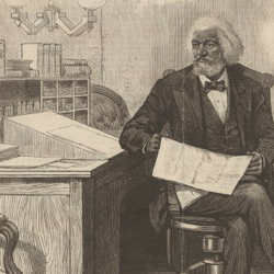 An illustration of Frederick Douglass sitting with a writing box atop his desk.