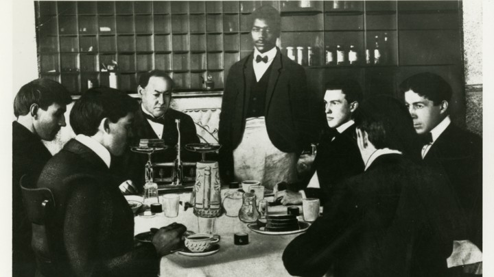 "A black-and-white photo of Harvey Wiley and members of the ""Poison Squad"" eating a meal"