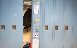 A row of lockers, with one open to show a backpack, textbooks, and interior decorations