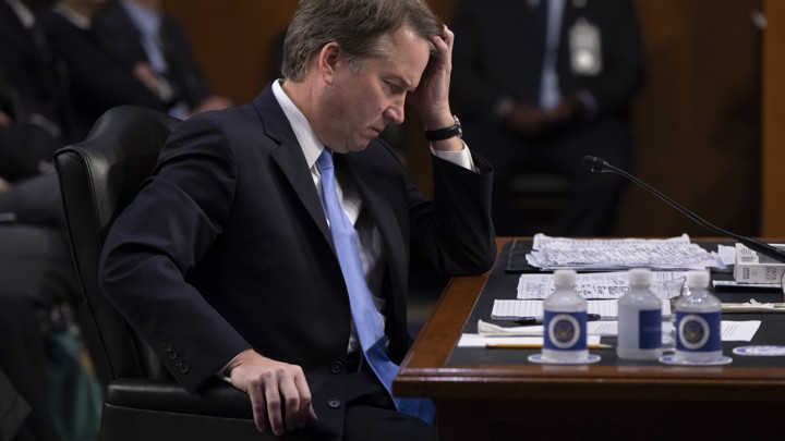 Brett Kavanaugh sits at a desk during his Senate hearing.