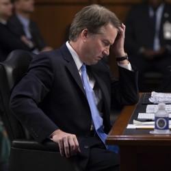 Brett Kavanaugh sits at a desk during his Senate hearing.