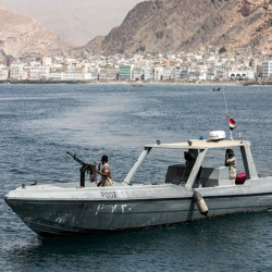 A boat with a Yemeni soldier manning a weapon patrols the coast of the port city Mukalla.
