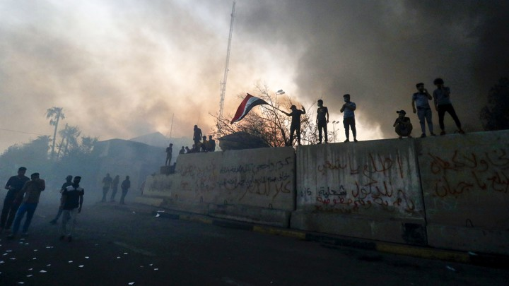Iraqi protesters wave a national flag while standing on barricades outside the burned-down headquarters of the local government in Basra on September 7.