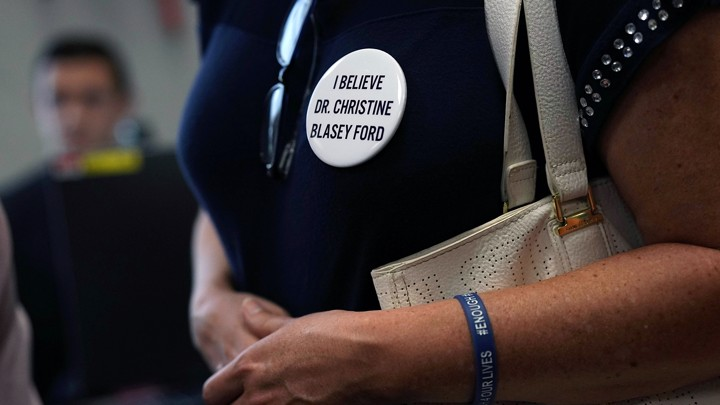 An activist wears a button in support of Christine Blasey Ford, who has accused Brett Kavanaugh of sexual assault at a high-school party more than 35 years ago.