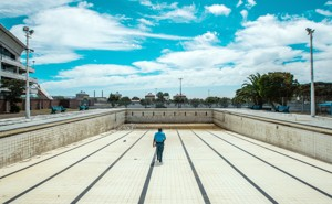 A man walks along the bottom of an empty public swimming pool near Cape Town.