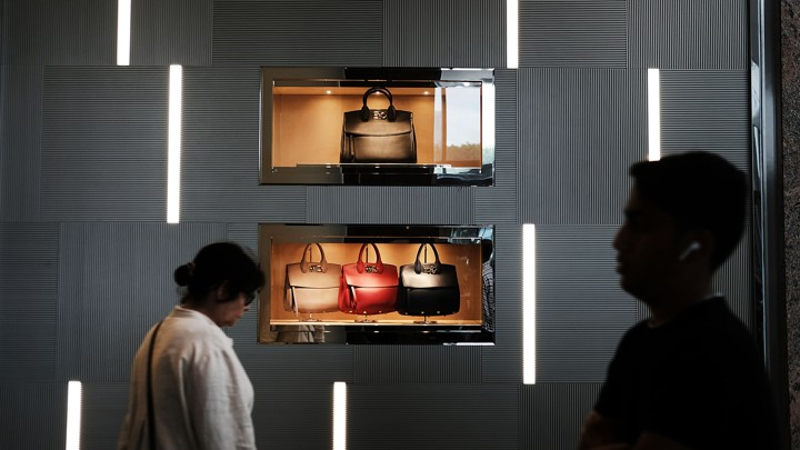 People walk in front of a display of handbags