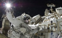 An astronaut works outside the International Space Station.
