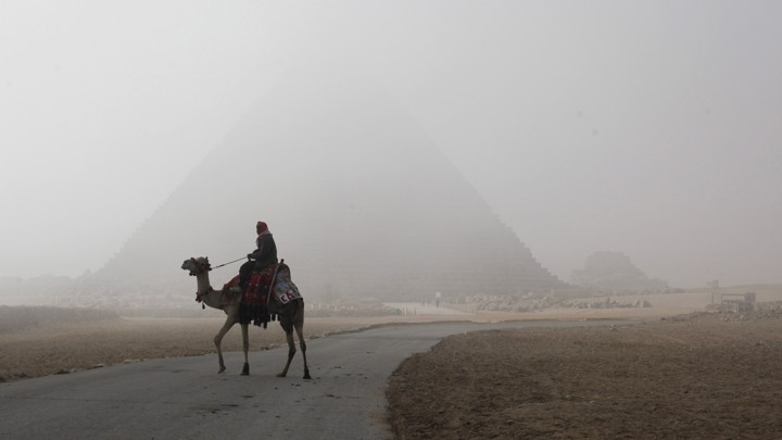 A photograph of a person riding a camel