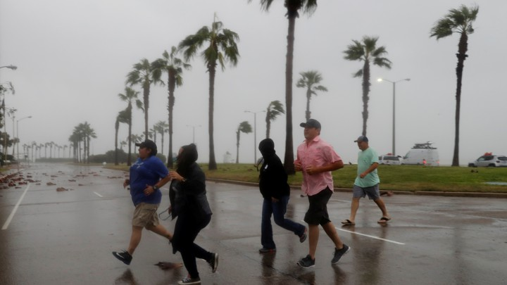 A group races across the street as winds from Hurricane Harvey escalate in Corpus Christi, Texas, on August 25, 2017.