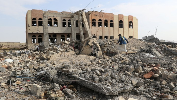 A man walks through the rubble of an air strike on a college in Saada, Yemen.