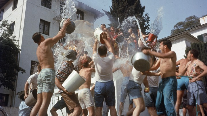 Fraternity brothers throw water at each other using buckets.