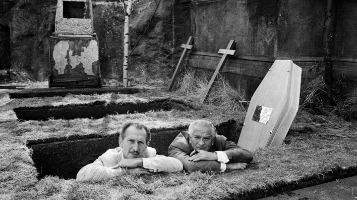 Two men stand in a freshly dug grave.