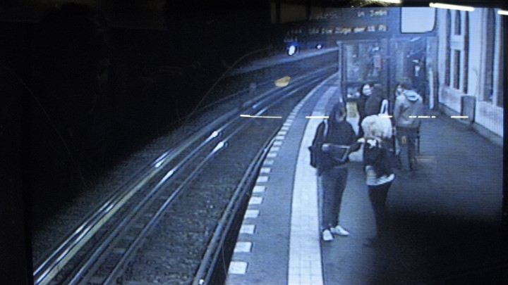 Grainy CCTV footage shows people standing at a train station.
