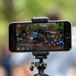 A person uses an iPhone on a tripod to broadcast an event to Facebook Live.