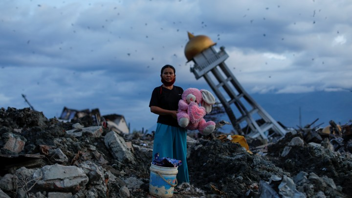 A woman holds a stuffed rabbit toy after it was found at her destroyed home where she said she had lost her three children, in Palu, Central Sulawesi, Indonesia.