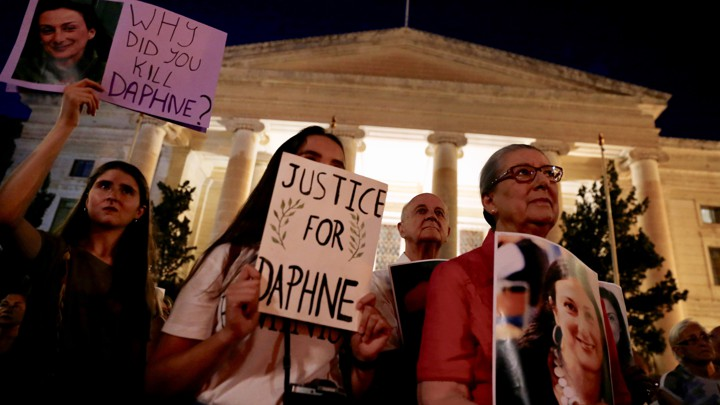 "Caruana Galizia's family members protest at Malta's Courts of Justice in August. Signs say ""Justice for Daphne"" and ""Why did you kill Daphne?"""